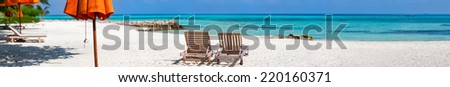 Panorama of a wooden lounge chairs on a beautiful tropical beach at Maldives - stock photo