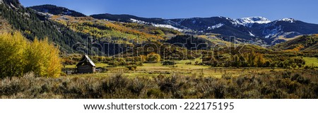 Panorama of abandoned homestead with brilliant fall colors along road to Capitol Peak near Aspen Colorado on sunny autumn afternoon - stock photo