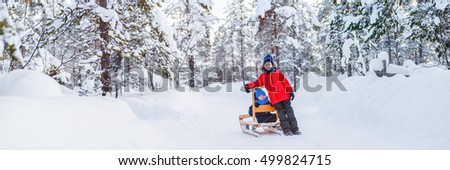 Panorama of adorable little girl and cute boy outdoors on beautiful winter day having fun playing in snow