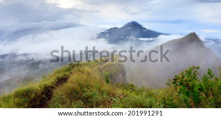 Panorama of Agung volcano and lake view from the of The Batur volcano crater in cloudy weather, Bali, Indonesia - stock photo