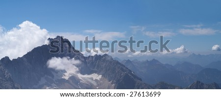 Panorama of Alpine mountains with cloudy skies and haze - stock photo