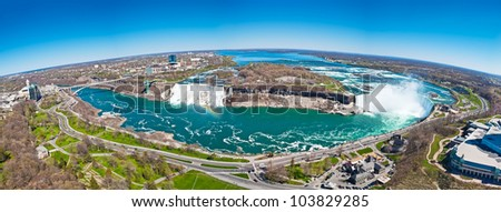 Panorama of American Falls with rainbow, Bridal Veil Falls and Horseshoe Falls, aka Canadian Falls, part of Niagara Falls on Niagara River on the border between United States of America and Canada - stock photo