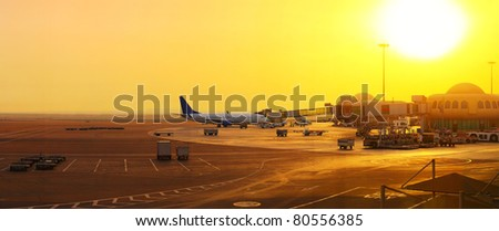 Panorama of an airport with plane near gate and part of a terminal at sunset light - stock photo