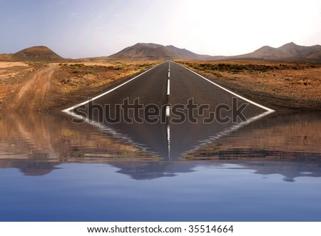 Panorama of an endless road with a nice reflection on the water - stock photo