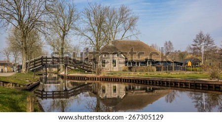Panorama of an old farm with reflection in the water in Giethoorn, Holland - stock photo