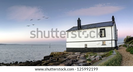 Panorama of an old house on the beach at Lepe in the New Forest. - stock photo