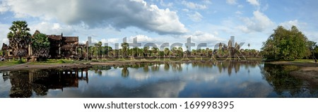 Panorama of Angkor Wat complex, Library building, Palm trees and their reflection one the pond against cloudy blue sky. - stock photo