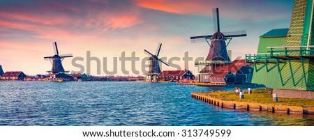Panorama of authentic Zaandam mills on the water channel in Zaanstad village. Zaanse Schans Windmills and famous Netherlands canals, Europe. Instagram toning. - stock photo