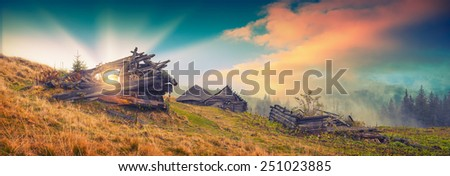 Panorama of beautiful sunrise in a rustic village with broken old wooden houses. Vintage colors - stock photo