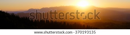 Panorama of beautiful sunset in mountains with silhouette of fir-trees. Summer sundown. Wonderful nature background. - stock photo