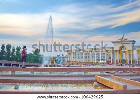Panorama of big fountain in National Park of first President of Kazakhstan. Young tourist admiring the sunset scenery. Almaty - stock photo