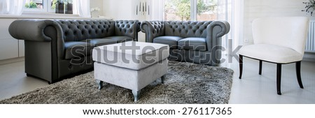 Panorama of black leather sofa in bright living room - stock photo