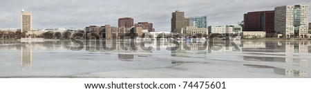 Panorama of Boston skyline reflected in the ice of the frozen river - stock photo