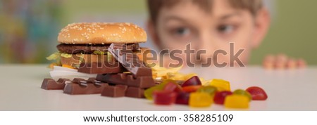 Panorama of boy and unhealthy junk food - stock photo