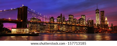 Panorama of Brooklyn Bridge, East River and Manhattan at sunset with lights and reflections. New York - stock photo