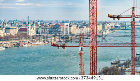 Panorama of Budapest with Elisabeth Bridge and liberty bridge in background, Danube river and construction cranes in foreground. Hungary, Europe.