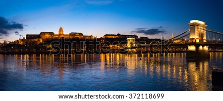 Panorama of Chain bridge in Budapest, Hungary, Europe. Blue hour in city. Sky and lights reflecting in waters of Danube river. Major Landmark and tourist attraction.