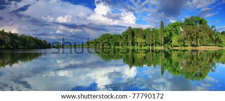 Panorama of cloudy sky reflection in the lake - stock photo