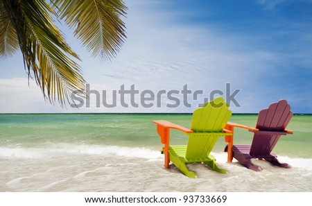 Panorama of colorful lounge chairs at a tropical paradise beach in Miami Florida. Beautiful aqua green waters of the ocean, hanging palm tree branches  and a blue sky in the background - stock photo