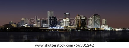 Panorama of downtown New Orleans after sunset from across Mississippi River - stock photo