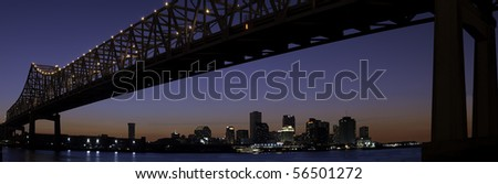 Panorama of downtown New Orleans after sunset with Mississippi River bridge - stock photo