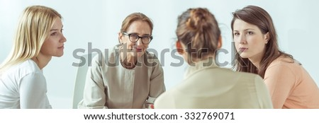 Panorama of female psychologist helping her stressed and depressed patients  - stock photo