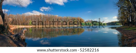 Panorama of forest reflection in limpid lake at autumn sunny day