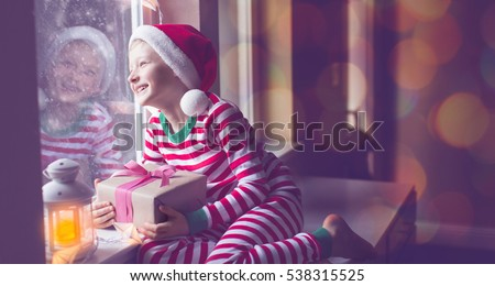 panorama of happy boy holding wrapped gift sitting cozy at home looking out the window while snowing waiting for christmas miracle, christmas lights and decorations, holiday concept, toned image