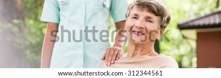 Panorama of happy elderly woman having private medical care - stock photo