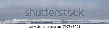 Panorama of incoming waves and sea foam on beach at Seaside Oregon