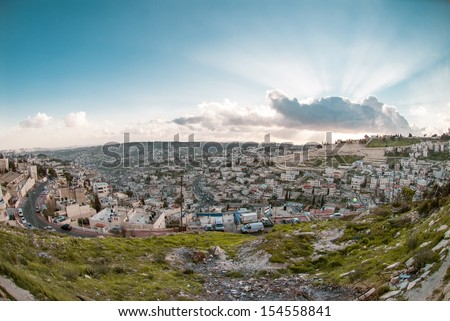 Panorama of Jerusalem from the Mount of Olives, with cloud in the sky and beautiful rays of sun - stock photo