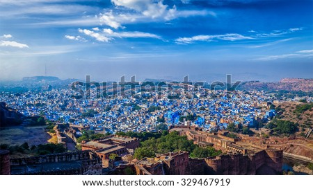 "Panorama of Jodhpur, also known as ""Blue City"" due to the vivid blue-painted Brahmin houses. View from Mehrangarh Fort (part of fortifications is also visible).  Jodphur, Rajasthan, India - stock photo"