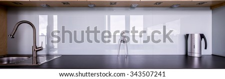 Panorama of kitchen sink and black solid worktop - stock photo