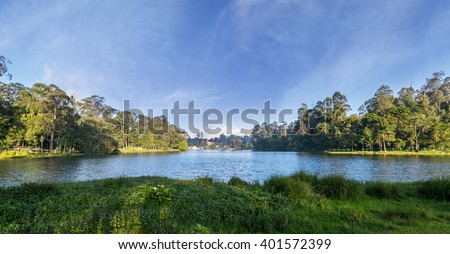 Panorama of Kodaikanal Lake, also known as Kodai Lake is a man-made star shaped lake located in Tamil Nadu, India. Beautiful lake and view, rippled water reflecting the blue color sky. - stock photo