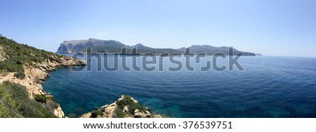 Panorama of la Dragonera Island, Mallorca, Spain across a tranquil ocean on a sunny blue sky day in a tourism concept