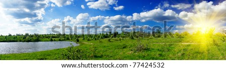 Panorama of lake, meadow and blue sky in the springtime. - stock photo