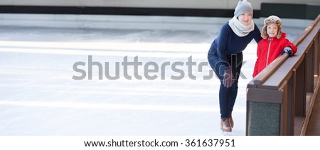 panorama of little boy and his mother ice skating together at outdoor skating rink, having winter vacation fun - stock photo