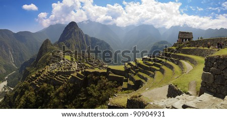 Panorama of Machu Picchu, Guard house, agriculture terraces, Wayna Picchu and surrounding mountains in the background. - stock photo