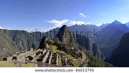 Panorama of Machu Pichu with Huayna Picchu, rainforest jungle and mountains with blue sky in the background - stock photo