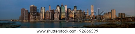 Panorama of Manhattan skyline early in the morning as the sun is rising creating a glowing city - stock photo