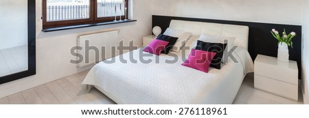 Panorama of modern bedroom interior with white double bed - stock photo