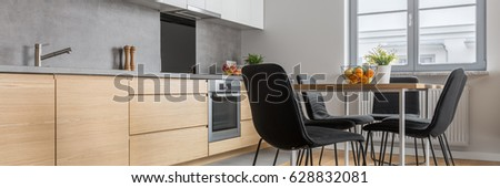 Panorama of modern kitchen with long countertop, table and chairs