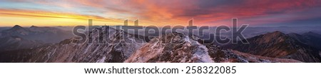 panorama of mountains covered with light snow. all lit yellow light of the sun. the sky beautiful red clouds - stock photo