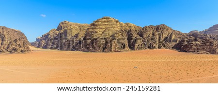 Panorama of Mountains of Wadi Rum desert in Jordan, a 4x4 car is cruising through the desert - stock photo