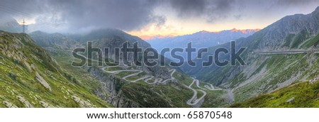 Panorama of old road with tight serpentines on the southern side of the St. Gotthard pass bridging swiss alps at sunset - stock photo