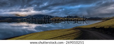 Panorama of overcast sky over mountains reflected in lake at daybreak with a winding road in the foreground, Landmannalaugar, Iceland. - stock photo