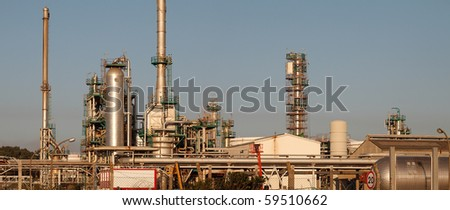 Panorama of part of a big oil refinery and powerplant - late evening light - stock photo