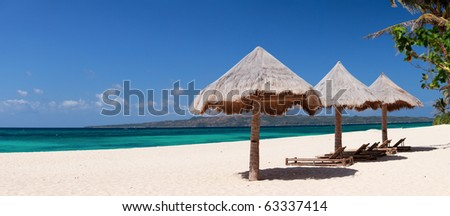 Panorama of perfect tropical beach with sun umbrellas