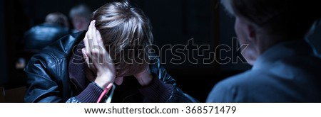 Panorama of policewoman interrogating upset young arrested man - stock photo