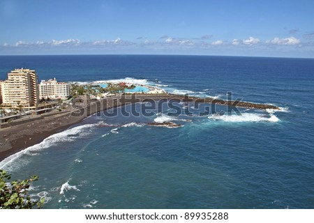 Panorama of Porta De La Cruz showing bay beach surf and buildings from up high